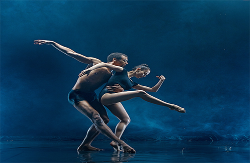 Young couple of ballet dancers dancing under water splash and drops. Young caucasian and afro american models. Man and woman dancing together. Ballet and contemporary choreography concept. Art photo