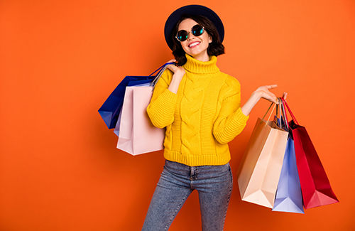 Photo of nice charming girl attractive joyful girl having just ended up shopping and being, overjoyed and cheerful while isolated with orange background